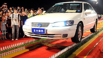 7793_src Китаец установил рекорд, проехав на автомобиле по двум рядам стеклянных бутылок